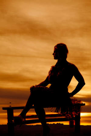 A woman in a dress is sitting on a bench in the sunset silhouetted. photo