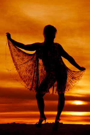 A woman silhouetted in the sunset holding out her see through dress.