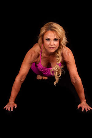 A woman in a pink top doing a pushup photo