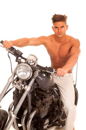 a man without a shirt on sitting on his motorcycle. photo