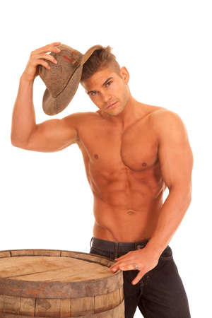 poised: A man with no shirt on putting his hat on his head. Stock Photo