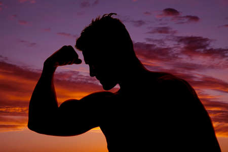 a silhouette of a man flexing  and looking down at his bicep.