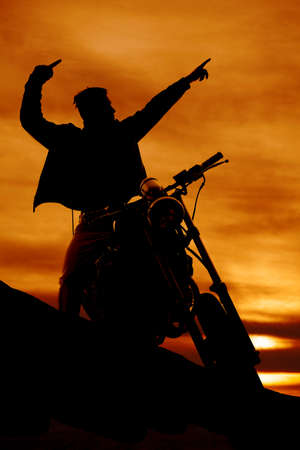 a silhouette of a man on a motorcycle pointing. Stock Photo