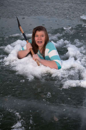 axe girl: A girl in a hole in the frozen lake holding on to an axe Stock Photo