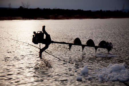 auger: a silhouete of an ice auger on a frozen lake. Stock Photo