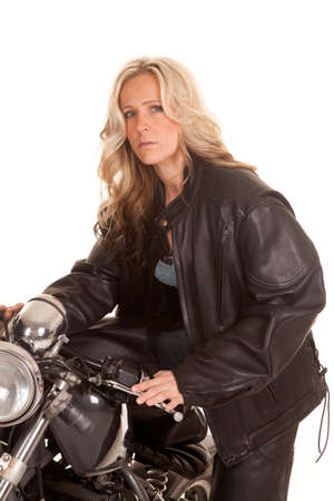 A woman in black leather sitting on a motorcycle. photo