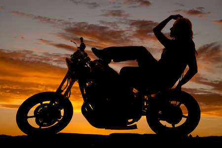 A silhouette of a woman sitting back on a motorcyle. photo