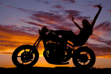 A silhoeutte of a woman sitting on a motorcycle throwing her arms up into the sky. photo