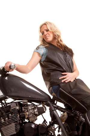 A woman sitting on a motorcycle in leather and a worried expression. photo