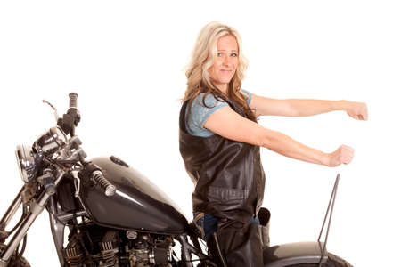 A woman in leather is sitting backwards on a motorcycle. photo