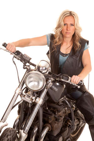 A woman in leather looks serious on her motorcycle. photo