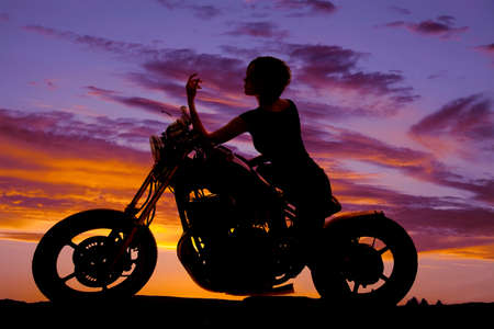 a silhouette of a woma on her motorcycle resting. photo