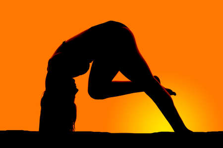 bent over: A silhouette of a woman bent over in the sunset.