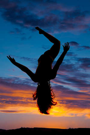 A silhouette of a woman in the sunset free falling. photo