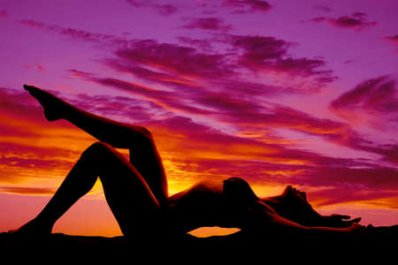 A woman in a bikini silhouetted by the sunset laying on her back. photo