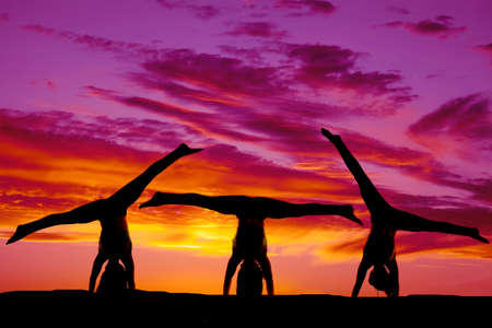 Silhouettes of a woman doing handstands in three positions. photo