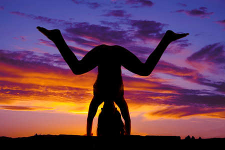 knees bent: A woman in the sunset silhouette doing a hand stand with knees bent. Stock Photo