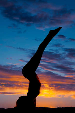 A silhouette of a woman on her arms with her legs up in the air. photo