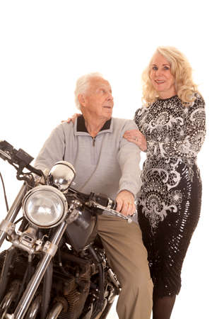 An elderly couple dressed up with a motorcycle.