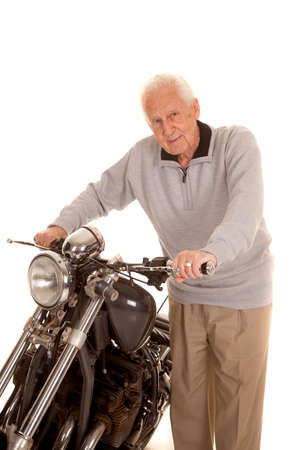 An old man standing by a motorcycle holding onto it. photo