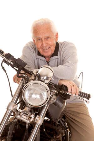 An elderly man sitting on a motorcycle smiling. Standard-Bild