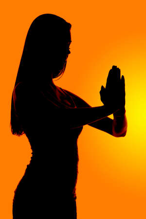 reverence: a silhouette of a woman praying in reverence