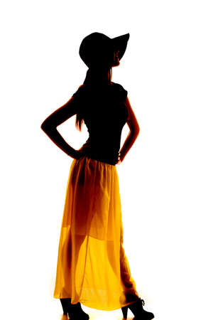 a silhouette of a woman in her see through skirt and floppy hat on her head.