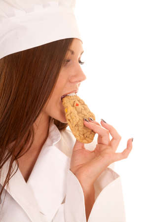 a woman baker tasting her cookie to see if it is good.