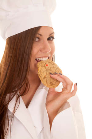 a woman baker taking a bite out of a cookie
