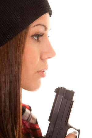a close up of a woman blowing on the tip of her gun.