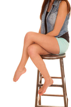 a woman sitting on a stool in her shorts showing off her legs. photo