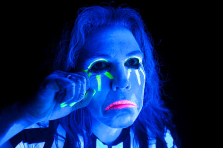 A woman lit up by a black light is sad. photo