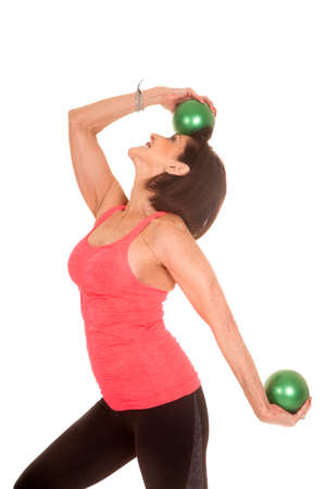 An older woman working out with weighted green balls. photo