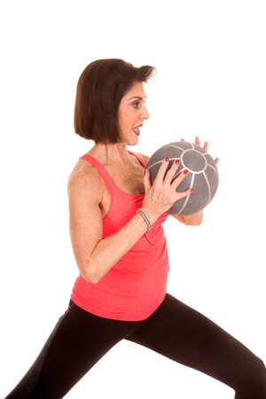 An older woman working out with a medicine ball. photo