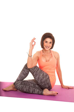a woman stretching out her legs giving the okay sign with her hand. photo