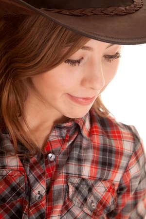 cowgirl hat: Una mujer en su camisa a cuadros y sombrero de vaquera mirando hacia abajo Foto de archivo