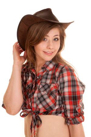 cowgirl hat: una mujer en su camisa a cuadros y sombrero de vaquera mirando y sonriendo.