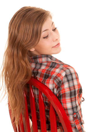a woman in her red chair in her plaid top looking over her shoulder. photo
