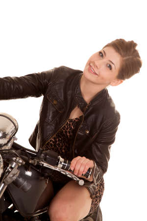 a woman with a smile on her face sitting on a motorcycle in her leather jacket.