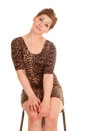 a woman in her leopard dress sitting on her stool with a small smile on her lips. 免版税图像