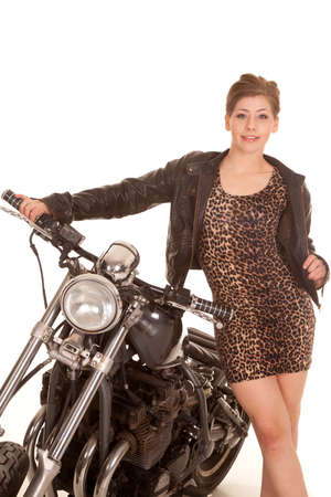 A woman in her leopard dress and leather jacket standing by her motorcycle. photo