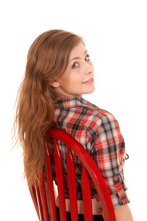 a woman sitting in a red chair in her plaid western top looking over her shoulder photo