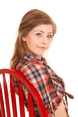 a girl in her western clothing sitting in a red wooden chair. photo
