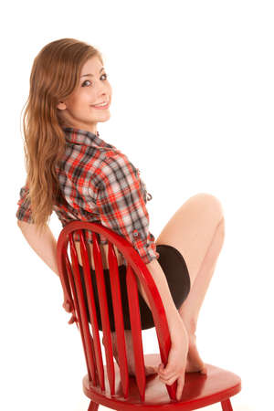 a woman in her western top sitting on a chair smiling. photo