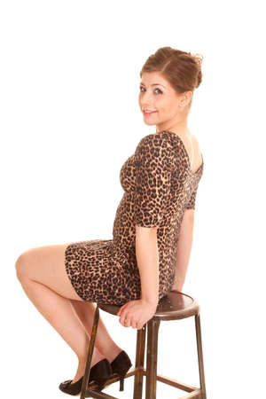 stool: A woman sitting on the stool looking over her shoulder. Stock Photo