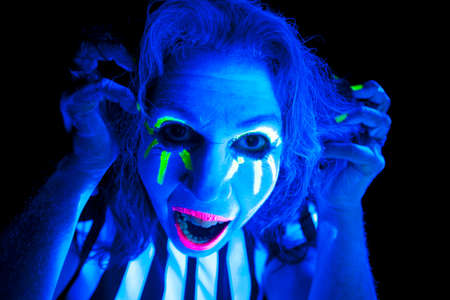 ultraviolet: A woman glowing in the ultraviolet light with a crazy expression. Stock Photo