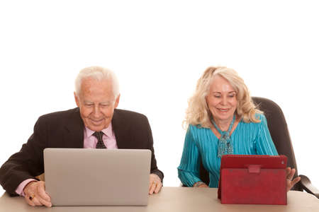 An older couple business people working together on a tablet and computer. photo