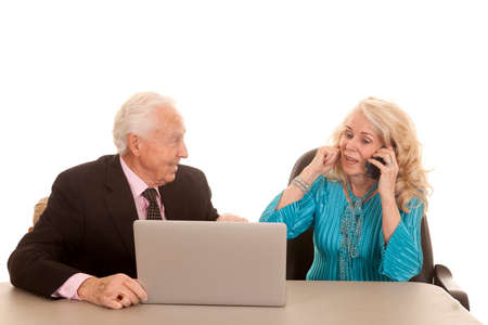 a older man working on the computer while the older woman is plugging her ear so she can talk on the phone. photo