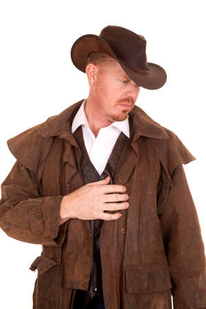 A cowboy looking down to the side, wearing his duster. photo