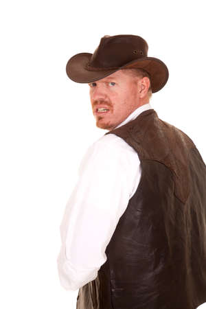 a cowboy in his vest and hat looking over his shoulder with a mad expression on his face. photo